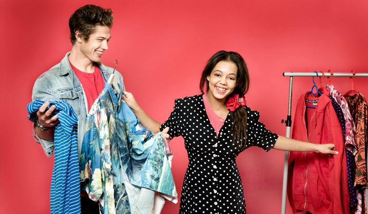 Två personer skrattar och håller i kläder bredvid en klädställning