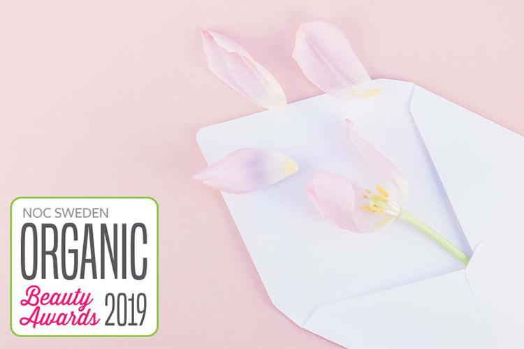 Texten Organic Beauty Awards 2019 mot rosa bakgrund, en tecknad rosa blomma till höger