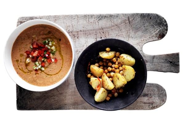 Två skålar på en skärbräda. Soppa i den vänstra, potatis i den högra