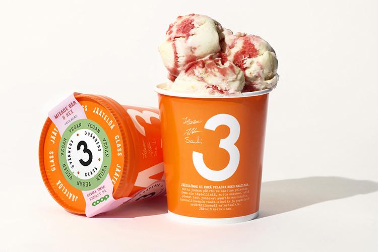Två orangea glassbägare, en liggande med lock, den anta med glass som sticker upp, en vit 3:a på förpackningen