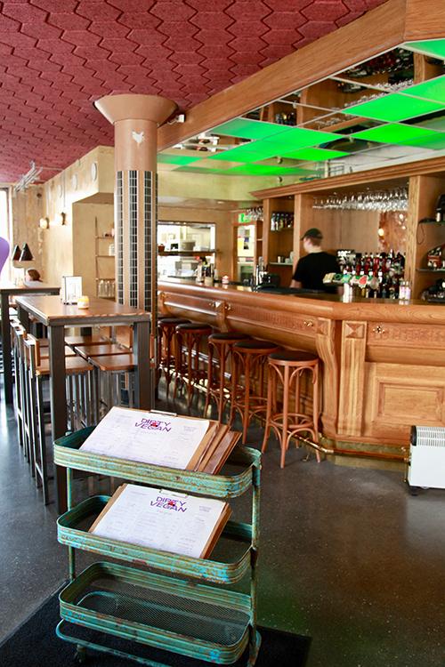 En bar i trä, höga bord med barstolar till vänster, gröna rektangulära lampor i taket
