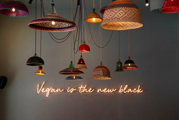 """Lampor hänger från taket och på väggen står det """"Vegan is the new black"""""""