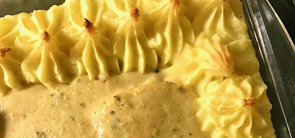 Spritsat potatismos runt kanten på en ugnsform, sås bredvid