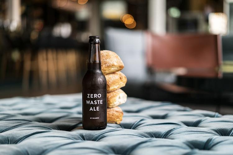 En brun ölflaska på ett bord, fyra frallor bredvid