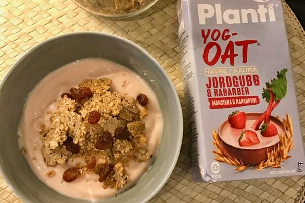 Grå skål med rosa yoghurt med müsli, till höger Planti yoghurtförpackning jordgubb och rabarber
