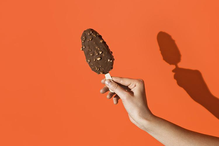 En hand håller fram en chokladöverdragen pinnglass mot orange bakgrund