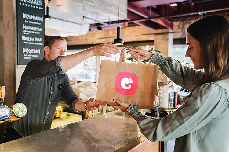 Butiksbiträde räcker över en papperskasse med logotypen för Karma till en kund