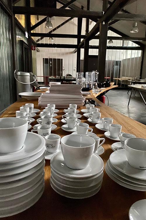 Kaffekoppar på fat uppradade på ett bord