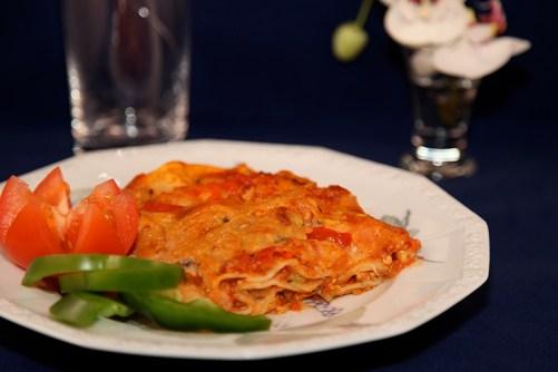 En tallrik med en portion lasagne, tomat och grön paprika vid sidan