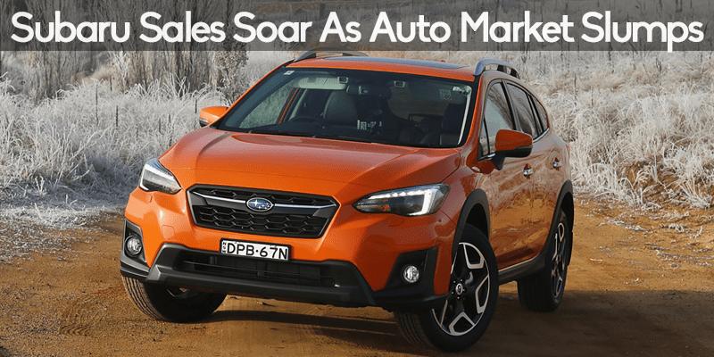 Photo of orange 2018 Subaru Crosstrek on dirt road during winter.