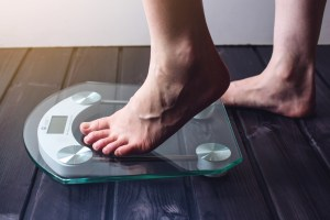 feet standing on weight scale on wooden floor