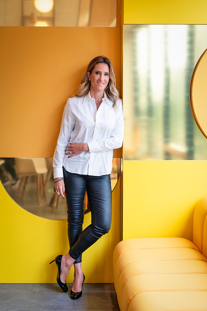 Karla Marques Felmanas poses standing and leaning against a wall. The whole setting is canary yellow and includes a sofa on the right. She wears black pants and a white shirt. He's got one of his legs bent and one of his arms against his belly.