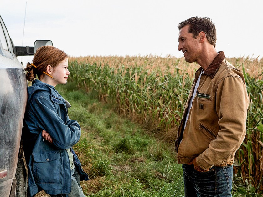 The image shows scene from the interstellar film. It is a father and a daughter, she is found at the door of a car with her back, looking at her father, who in turn has his hands in his pocket. In the background, there's a huge plantation.