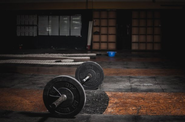 A barbell on the gym floor. Weight training is very important for endomorph bodybuilders.
