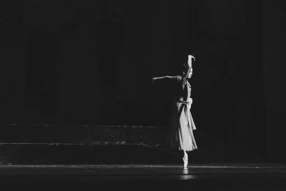A woman dances ballet en pointe with a black backgound