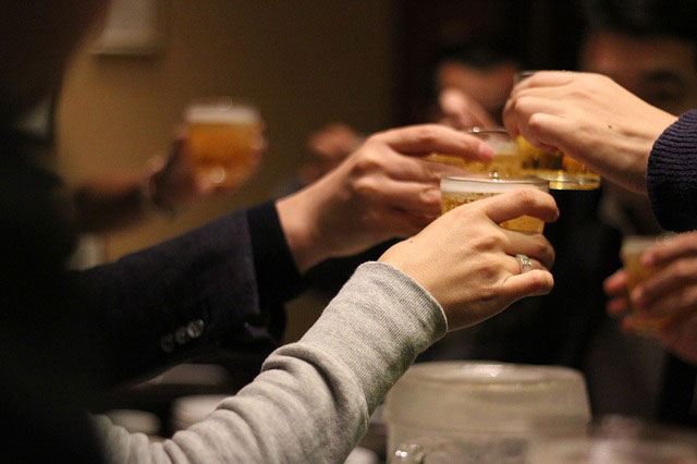 「かんぱ~い!」グラスを合わせて乾杯する人々