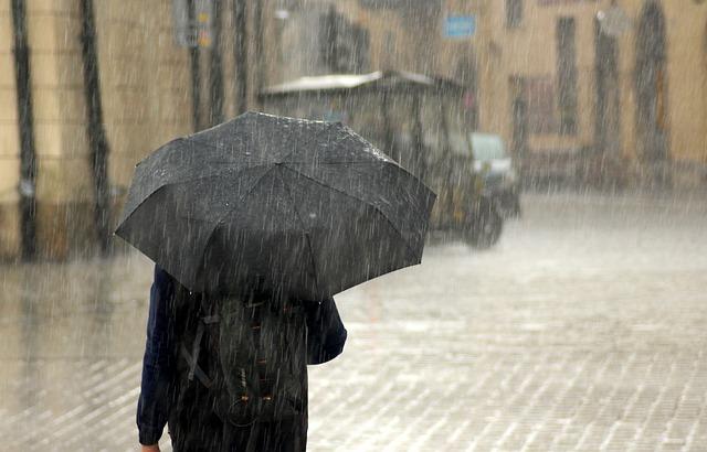 大雨の中黒い傘をさして歩く人