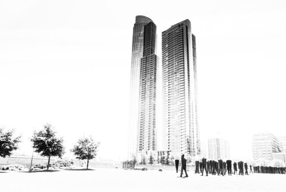 """106 headless and armless people in (supposed) movement. They are going in all directions in the park. Here, to me, it seems like they are waiting for people to get out of the huge sky scraper. Why though? What will they do to them? The overexposure here puts emphasis on just the one sky scraper and the sculpture, and somehow makes the """"they have interest in the dwellers of the building. They are waiting to do something"""" story."""