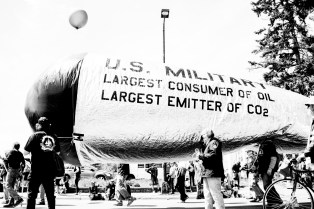 """A large ballon that has """" US Military: Largest Consumer of Oil, Largest Emitter of CO2"""" on it. It is held by various people."""