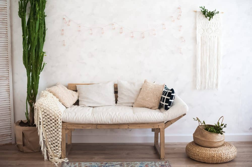 A small beige love seat with pillows