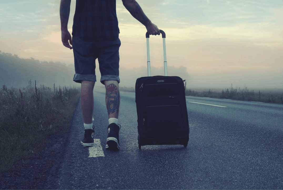 A man in shorts walks along the road with a suitcase