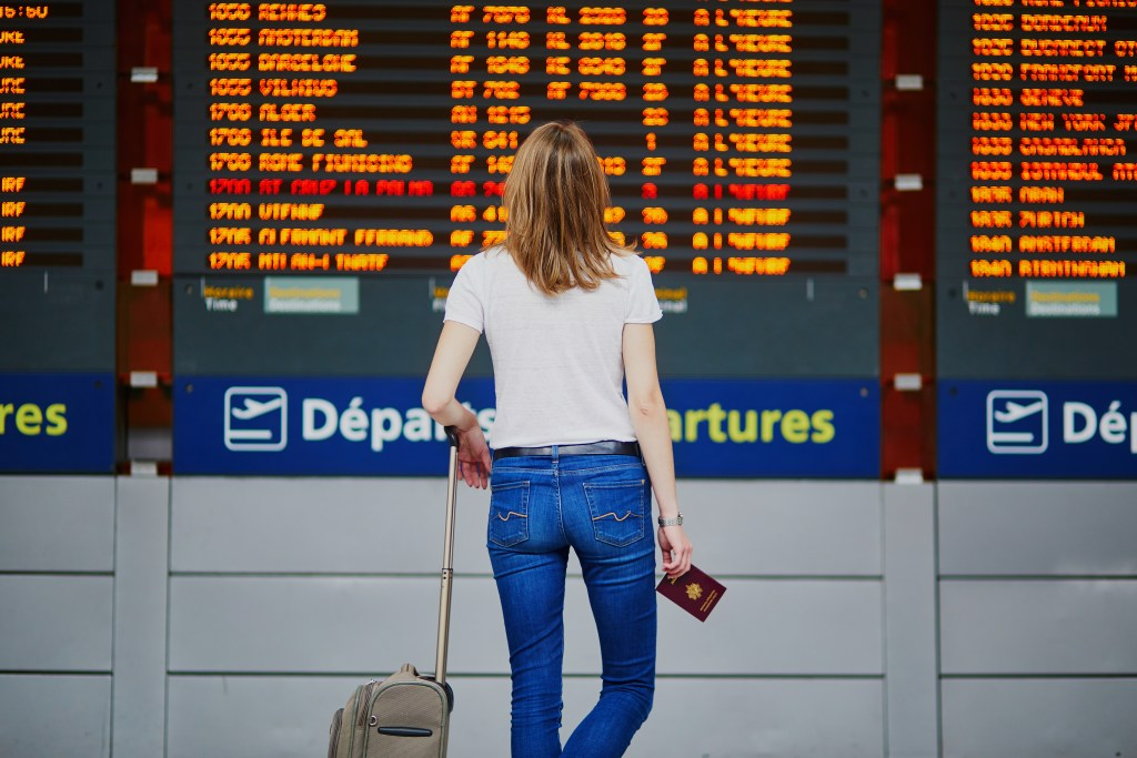 A woman looks at a board of departures at an airport