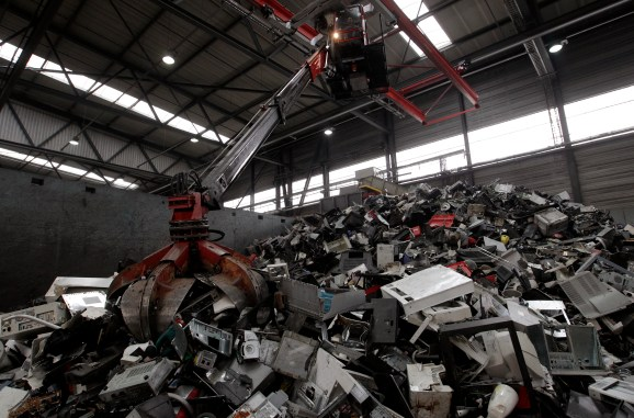 A worker in a crane uses a grappler to grab electronic scrap at a plant of Swiss recycling company Immark AG in the town of Regensdorf near Zurich April 8, 2013. REUTERS/Arnd Wiegmann (SWITZERLAND - Tags: BUSINESS EMPLOYMENT ENVIRONMENT) - RTXYD9E