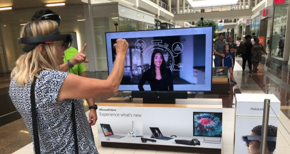 A Microsoft retail employee demonstrates HoloLens's pinch-to-select gesture during a shopping mall demo.