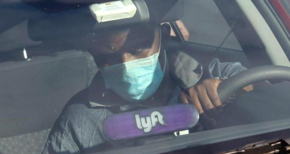 A Lyft driver wears a mask during the coronavirus outbreak, as he leaves passengers in the U.S. Capitol Hill neighborhood in Washington, U.S. April 1, 2020.