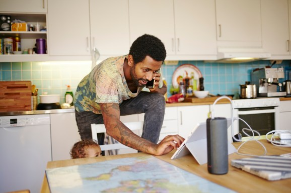 Father and son in kitchen juggling multiple devices
