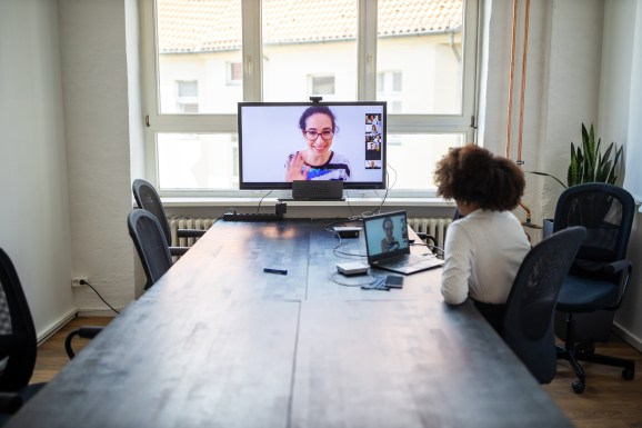 Businesswoman having a meeting with coworkers over a video call in office board room. Planning meeting over a video call in office