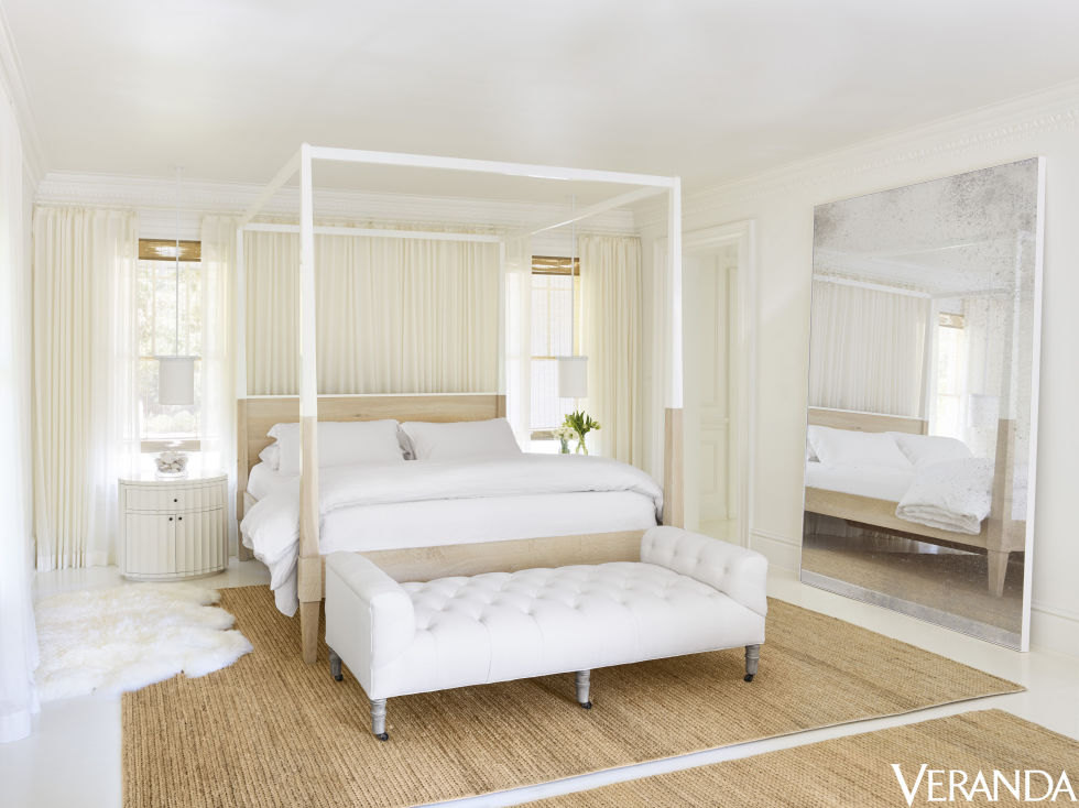 A large custom mirror makes this white and cream master bedroom feel bigger. The custom bed is topped with Restoration Hardware bedding, the bench by Cisco Brothers is in a Pindler fabric, the pendants are Kevin Reilly Collection, the woven rugs are from Restoration Hardware and the sheepskin is from Serena & Lily.