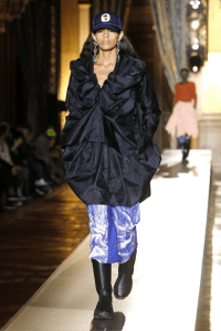 Andreas Kronthaler for Vivienne Westwood outfit in blue navy with anckle chunky boot girl wearing also a cap