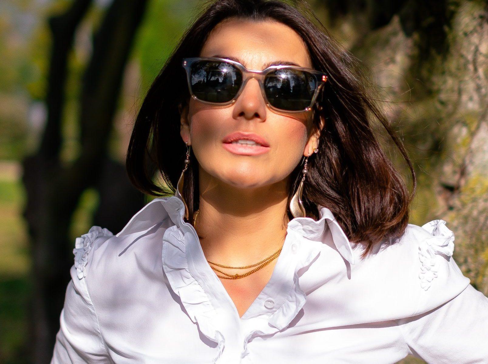 Vera Gallardo wearing white classic shirt with sunglasses in a garden next to a tree