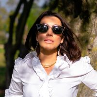 Vera Gallardo wearing white classic shirt with sunglasses in a garden next to a tree