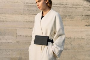 woman in a withe coat with a belbag black colour from von holzhausen brand