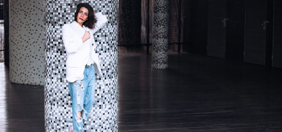 blogger Vera Gallardo standing up wearing a white blazer denim trousers with red lipstick and holding her hair in the back in front of a white and black wall