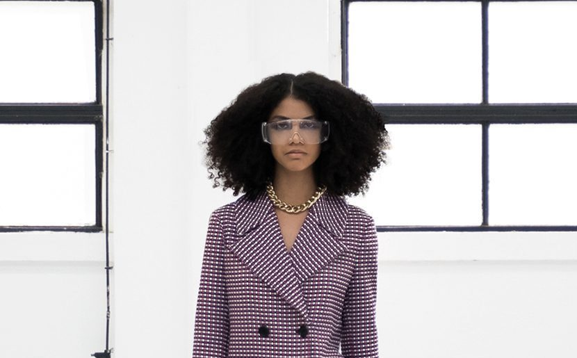 Gilberto Calzolari SS2021 cover - woman wearing a long coat in pink shade with black bottons with black and white stripes shoes and a golden necklace and wearing transparent glasses
