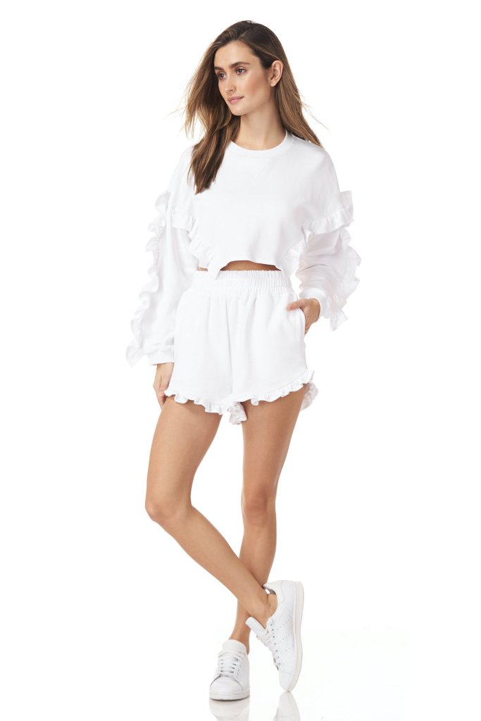 AMUR sustainable brand girl wearing a combo of sweat and shorts in all white, also wearing white sneakers long hair girl with very liht makeup