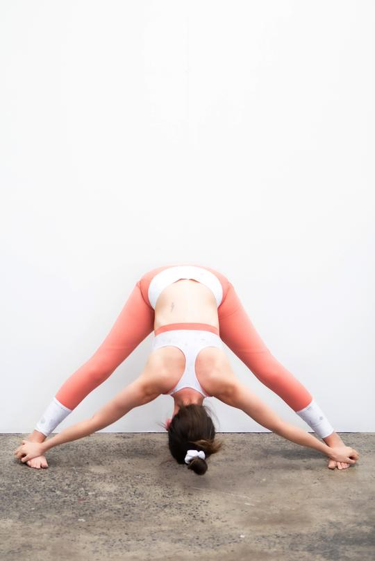 woman doing yoga with her legs wide open her arms down to her feets she is wearing a ELLE EVANS - Flora Sports Bra Reversible