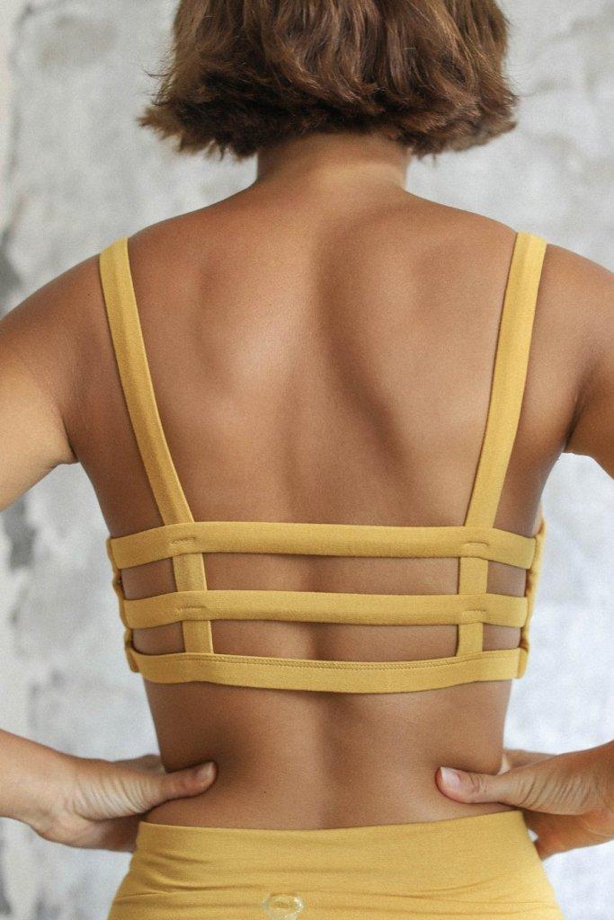 The Back of a girl wearing a indigo luna brand boxy crop in saffron collour