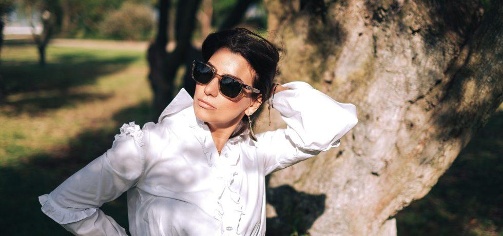 blogguer and influencer Vera Gallardo wearing white shirt and green glasses in a garden
