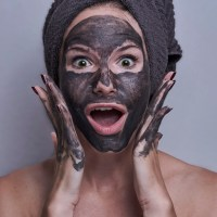 woman with a grey towel on her head and a facemask