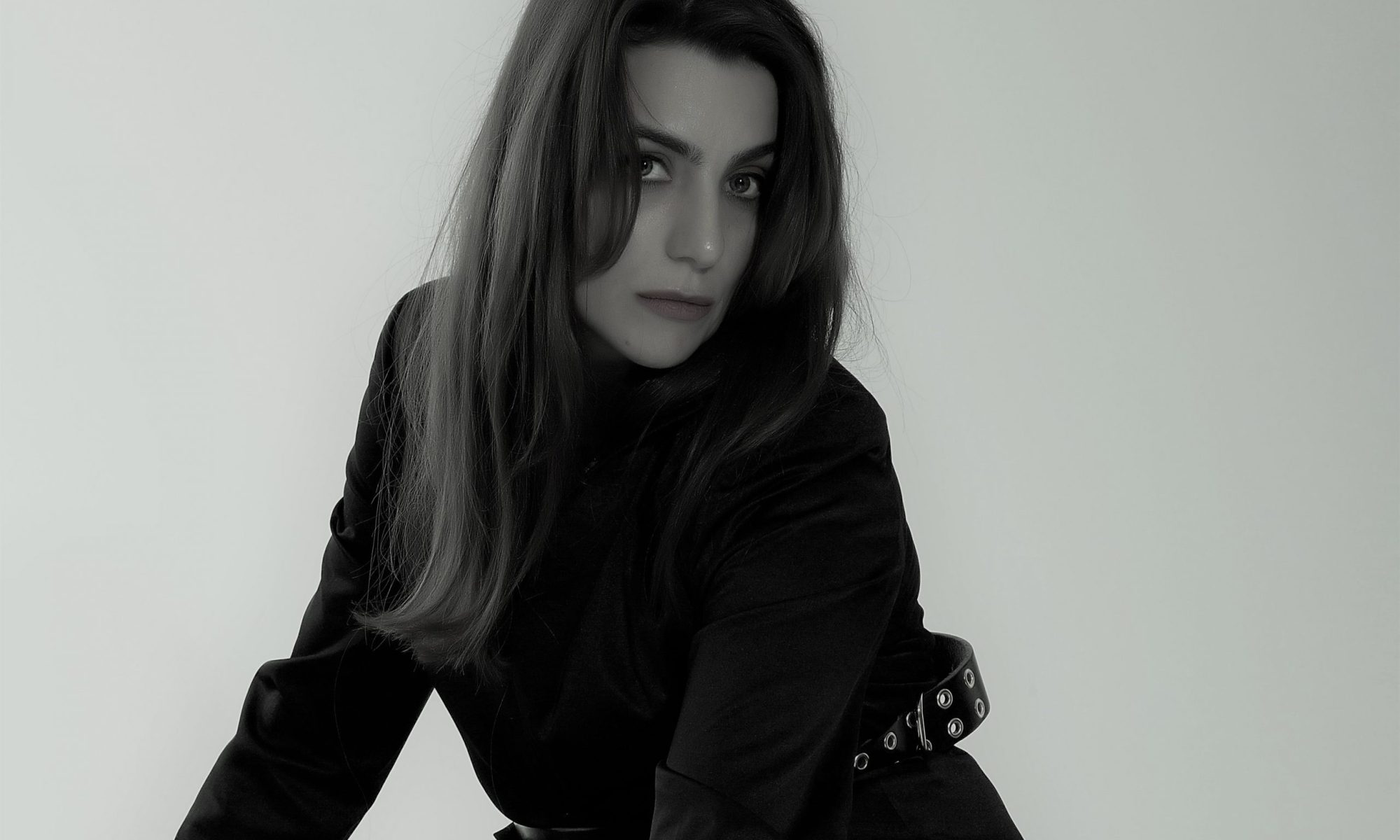 Vera Gallardo international fashion and beauty blogger wearing black blazer and golden belt over the waist and long hair in a blck and white image