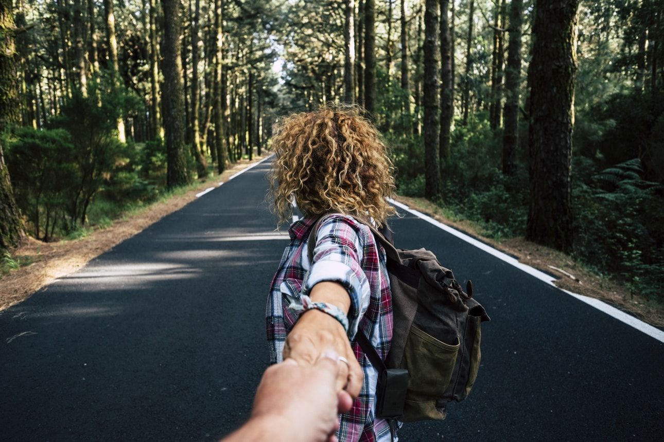 Couple travel together walking with backpack in a forest on a long asphalt road - man point of view -  holding hands with love and relationship - alternative holiday vacation in the outdoors nature