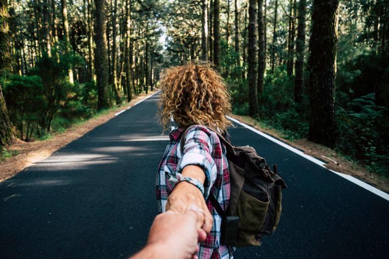 couple travel together walking with backpack forest long asphalt road