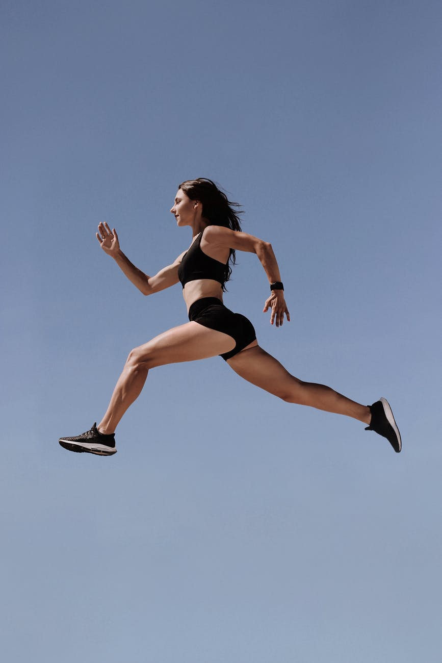 woman in black sports bra and black shorts jumping on air under blue sky