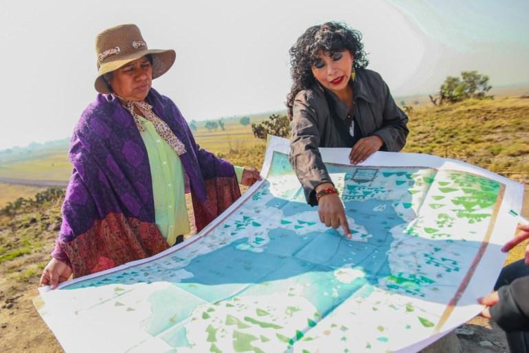 Marta y Adela explican la devastación de la plancha de concreto del NAICM a la orilla del cerro de Huatepec. Foto: Daliri Oropeza.