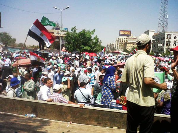 Anti-Military protestors gather at Rabaa Square.  They wave the Egyptian flag and hold up posters demonstrating the actions of the military against Morsi and the Muslim Brotherhood.