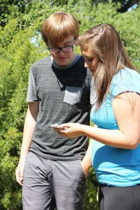 Junior Jamie Garcia and sophomore Sean Jawetz track a geocache using the Geocache app on their iPhone.